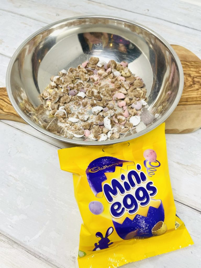 stainless steel bowl filled with crushed mini eggs read to go into mini egg cheesecake recipe