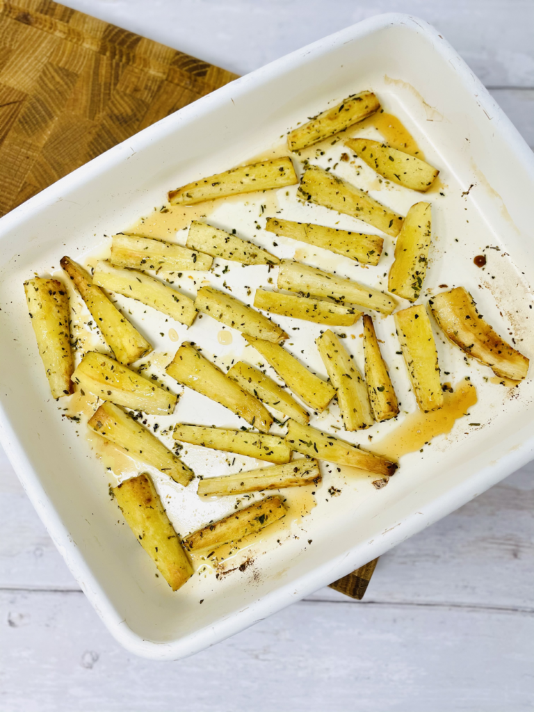 roast parsnips with honey and herbs in a white enamel roasting tin