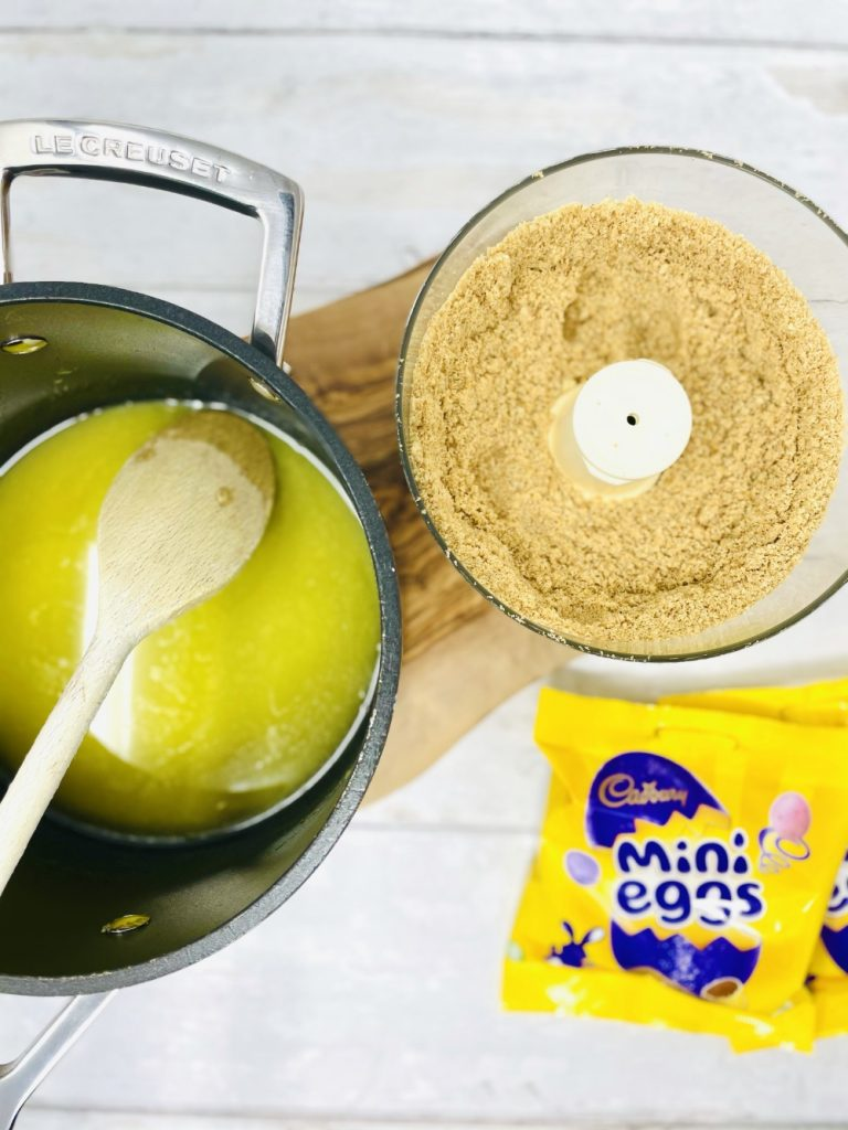 pan of melted butter and blender bowl filled with crushed digestive biscuits. Pack of mini eggs lay on table next to them