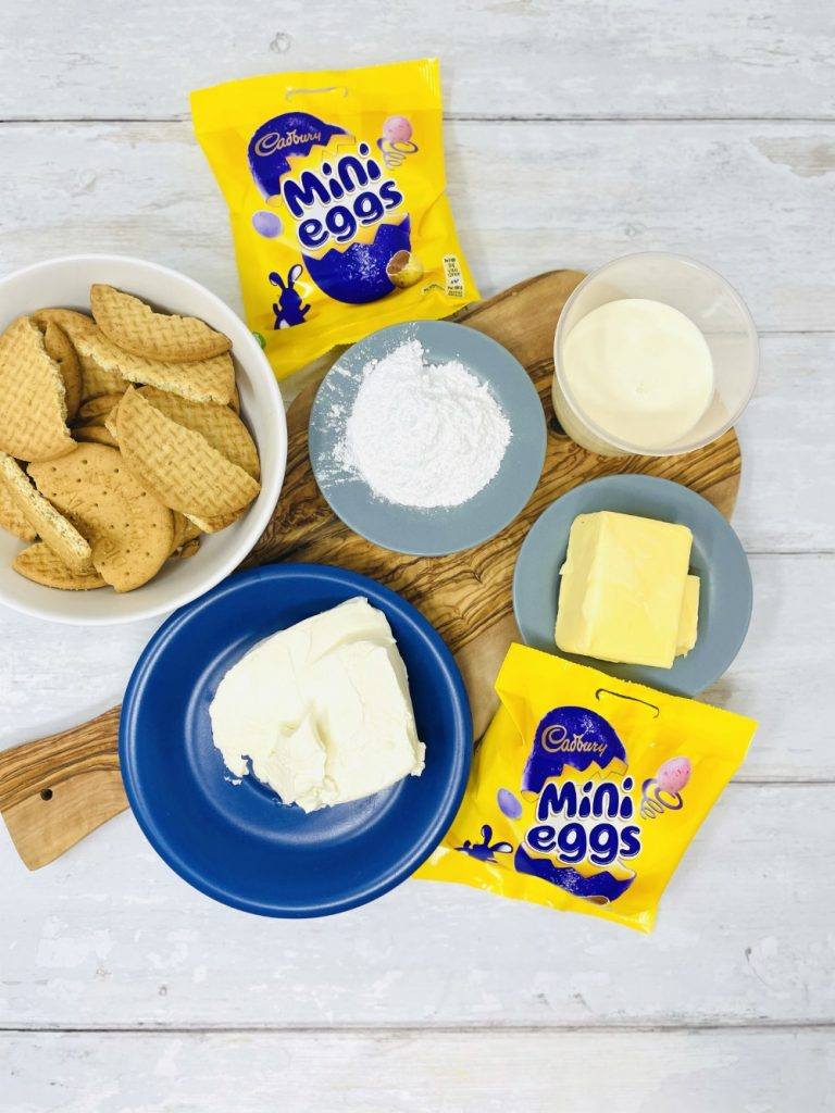 mini egg cheesecake ingredients - digestive biscuits, philadelphia cream cheese, double cream, icing sugar, mini eggs and butter on a wooden board