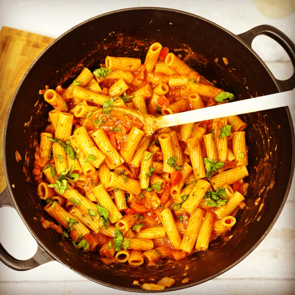 cheesy chorizo pasta in a large black le creuset pan