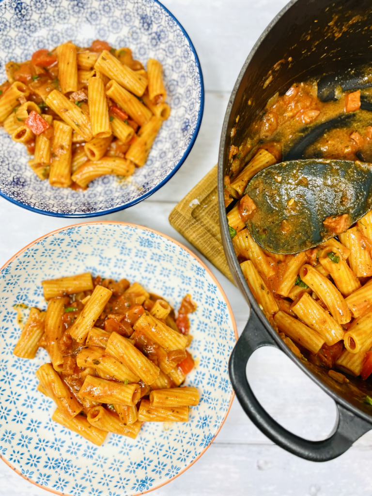 cheesy chorizo pasta in a large black le creuset pan being spooned into serving bowls
