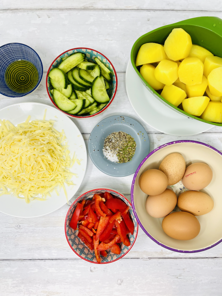 baked omelette ingredients on a white table - eggs, red peppers, grated cheese, boiled potatoes, seasoning and olive oil