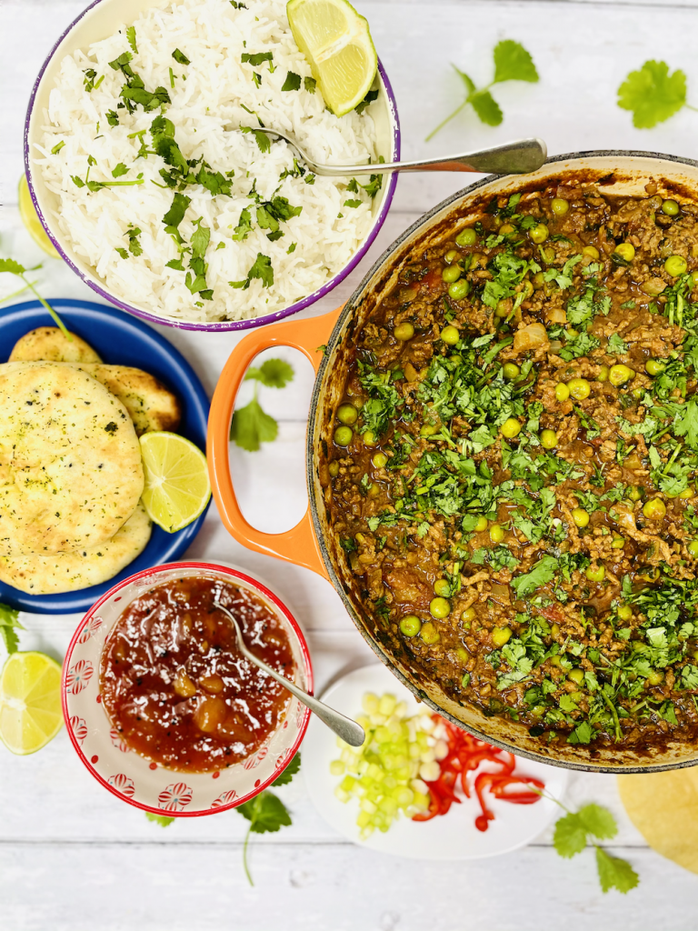 minced beef curry in a large Le Creuset casserole pan, served alongside fluffy basmati rice scattered with chopped coriander, mini garlic naan breads, mango chutney, chilli and onions chopped ready to scatter on the curry and popadoms