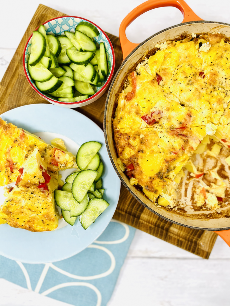 oven baked omelette cut into wedges and served on a plate with cucumber salad