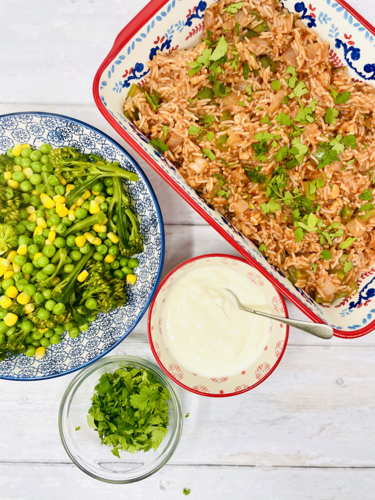 spicy prawn rice served in a rectangle dish alongside bowl of broccoli, peas and sweetcorn, bowl of natural yogurt and bowl of chopped coriander