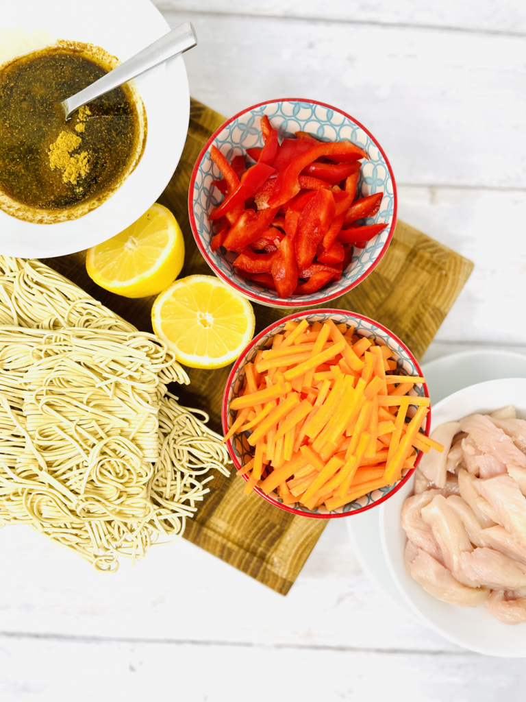 ingredients for spicy chicken noodles laid out on a white table ready to use - egg noodles, homemade stir fry sauce, pepper slices, carrot slices, lemon cut in half and bowl of raw chicken strips