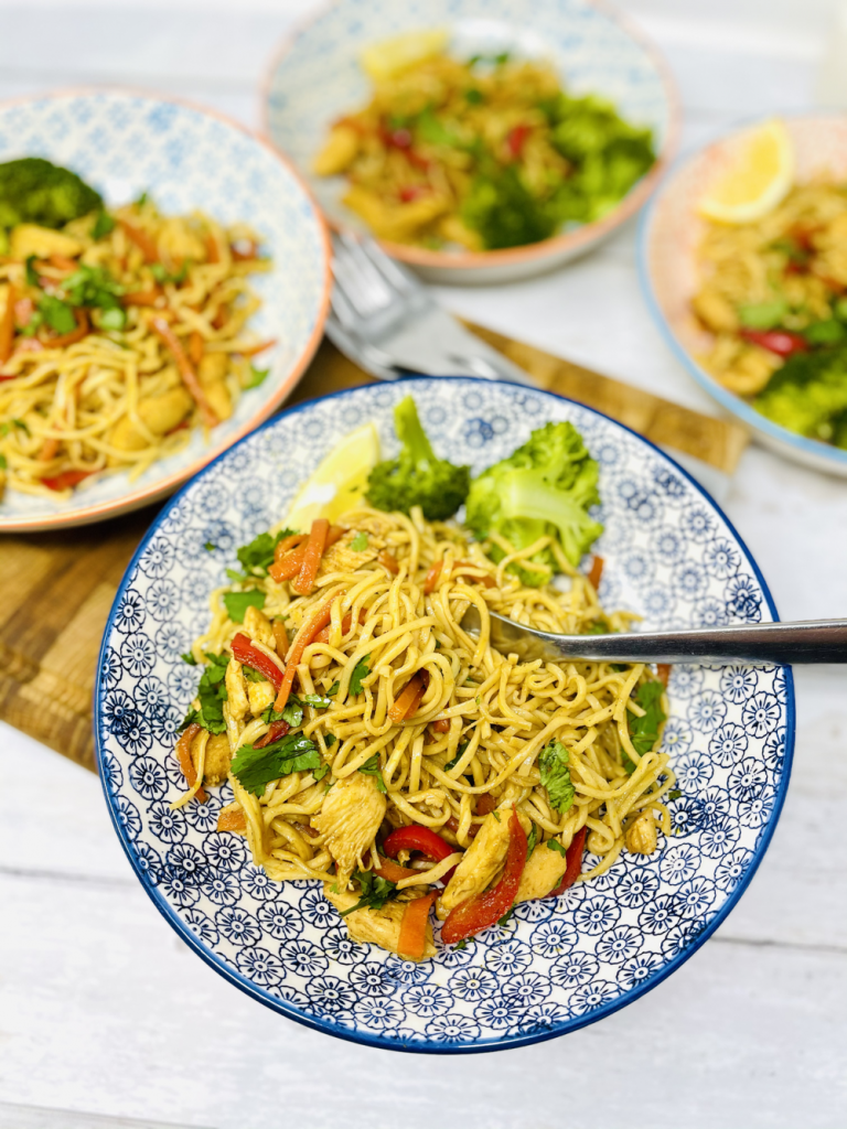 spicy chicken noodles served with a side portion of broccoli in geometric print bowls