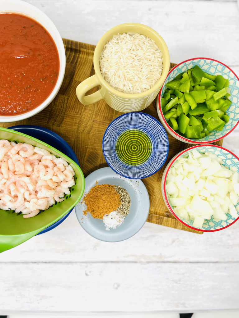 spicy prawn rice ingredients on a white table ready to cook with - pasta, defrosted cooked prawns, mug of rice, green pepper chopped, onion chopped, saucer of spices and small bowl of olive oil