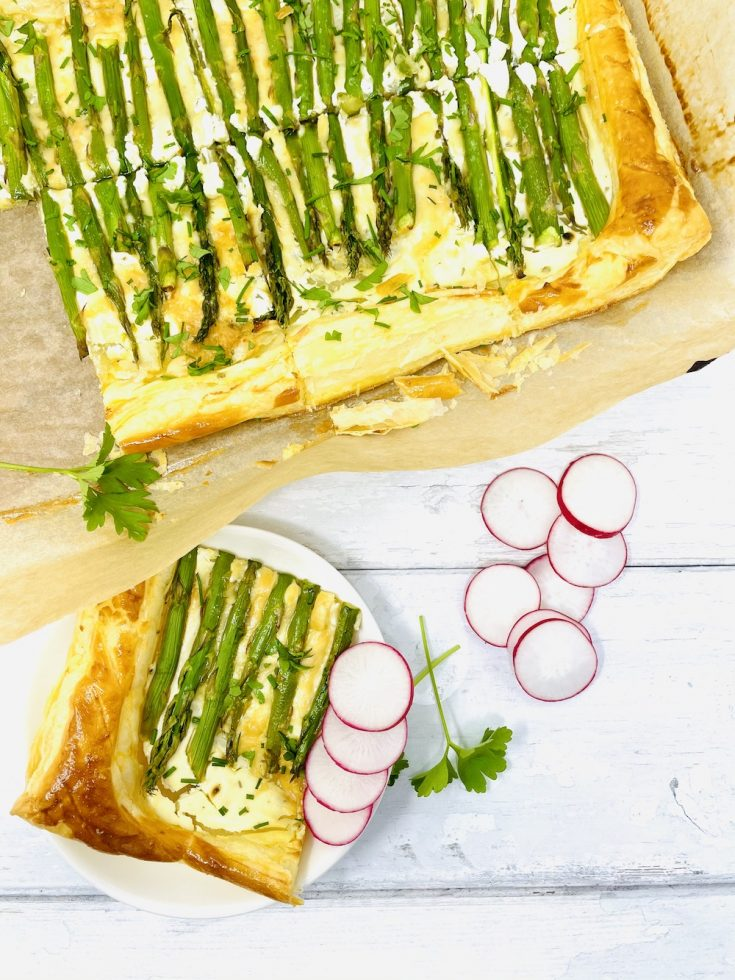asparagus tart sliced into eight with one slice served on a white plate with radish slices