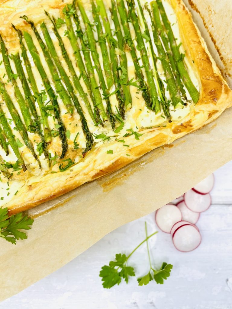 asparagus tart fresh from the oven served on a sheet of baking paper waiting to be sliced