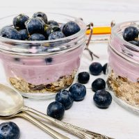 yogurt pot with blueberries, granola and Yeo Valley blueberry yogurt in a glass kilner jar with silver teaspoons by the side