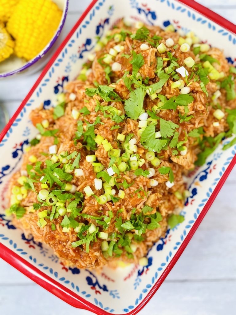 Cajun chicken and rice in a serving bowl sprinkled with chopped coriander and spring onions