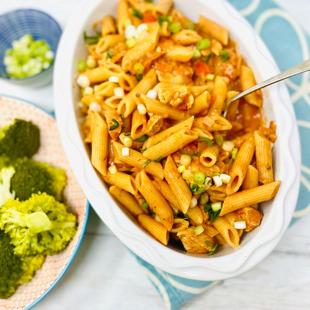 creamy cajun chicken pasta with penne in a serving bowl alongside broccoli and small bowl of chopped spring onions