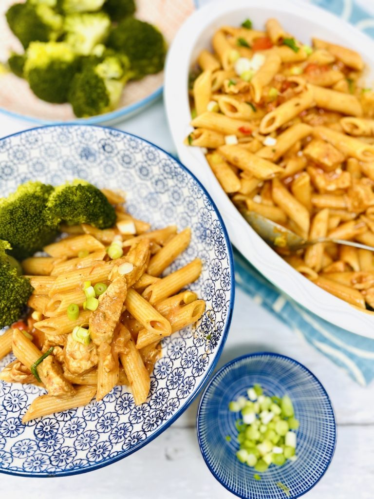 spicy chicken pasta made with penne served in pasta bowls with broccoli and sprinkled with spring onions
