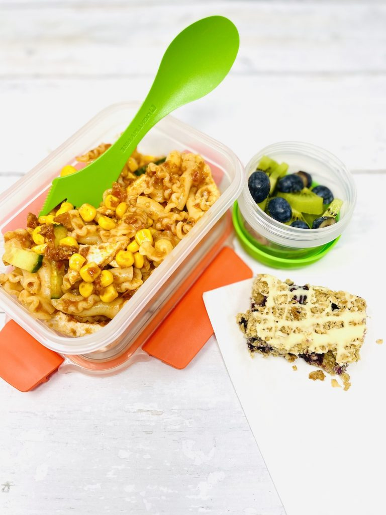 kids pasta salad with chicken in a Joseph Joseph food storage box next to a pot of kiwis and blueberries and a homemade blueberry flapjack