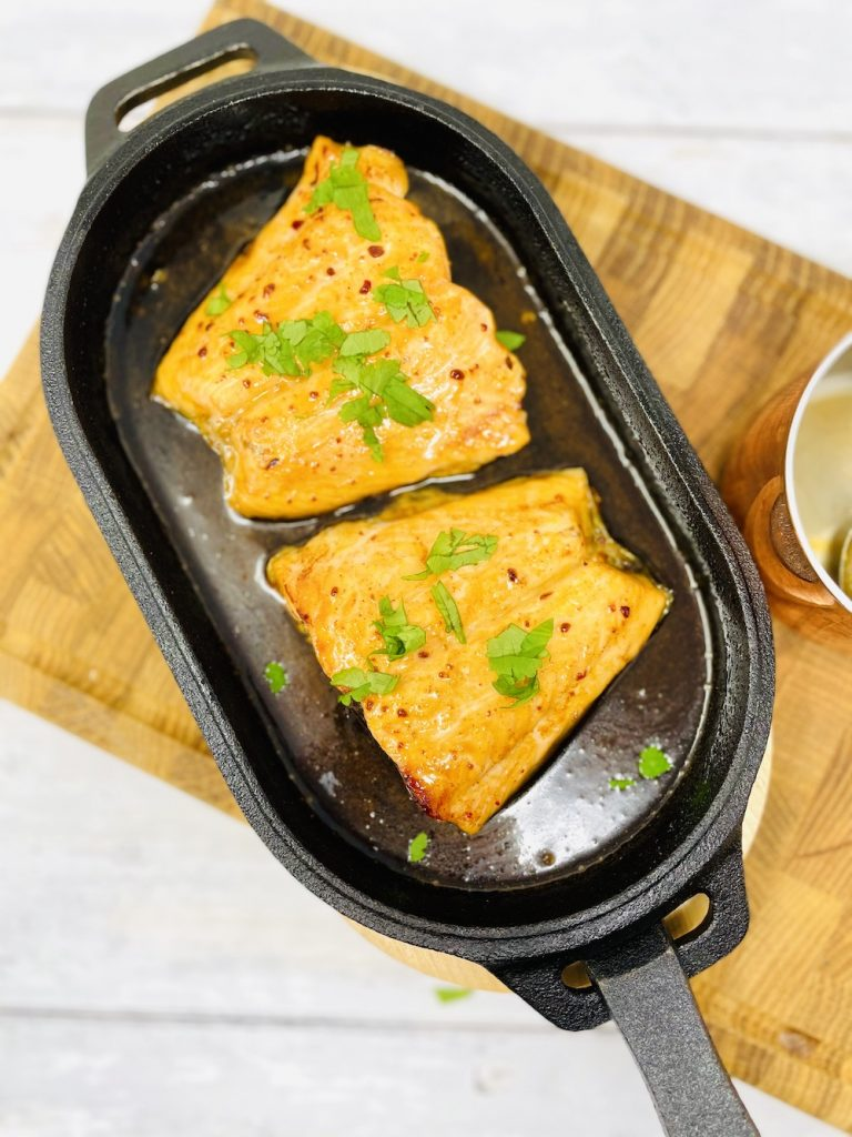 chipotle salmon cooked in the ooni pizza oven in a cast iron sizzle pan