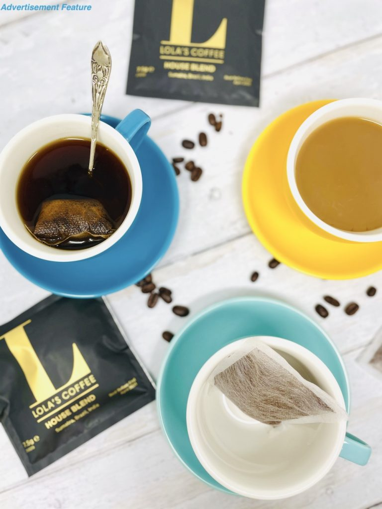 Lola's coffee bags steeping in boiling water, being stirred by a silver spoon