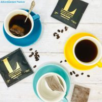 Lola's coffee bags in individual packs on a table with coffee bag brewed coffee in bright yellow and blue tea set