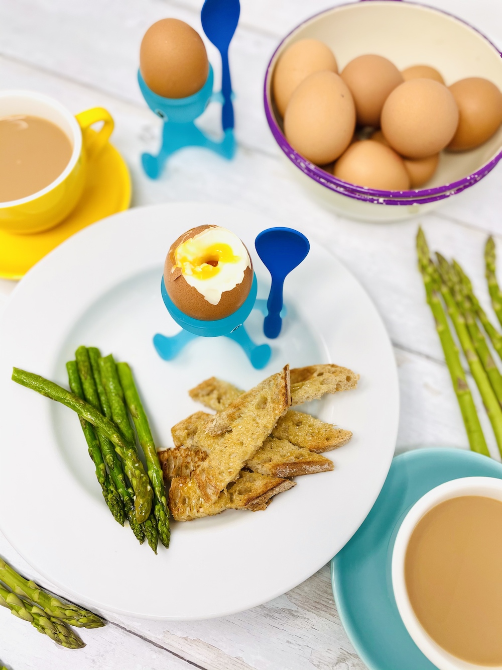 boiled egg and soldiers made from toast and asparagus. Served in alessi egg cups with cups of tea