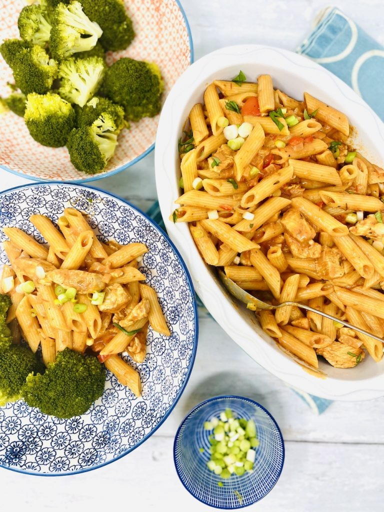 serving bowl of creamy cajun chicken pasta being served into pasta bowls alongside broccoli