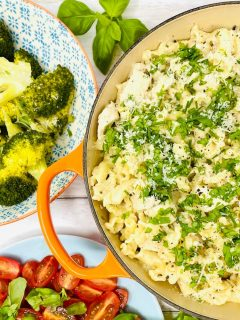 creamy garlic chicken pasta in a skillet pan sprinkled with chopped herbs. Side dishes of steamed broccoli and tomato salad scattered with basil leaves are alongside