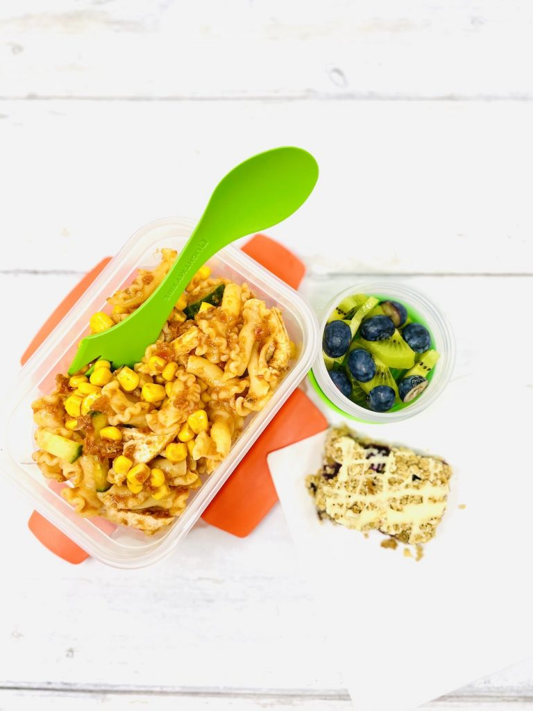 lunchbox pasta salad with chicken in a Joseph Joseph food storage box next to a pot of kiwis and blueberries and a homemade blueberry flapjack