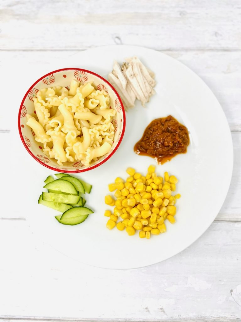 ingredients for lunchbox pasta salad with chicken - cold pasta, cucumber strips, handful of sweetcorn, sliced chicken and red pesto