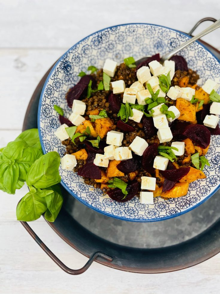 Puy lentil salad with feta cheese, roasted sweet potatoes, baby beetroot and basil leaves in a blue and white patterned bowl on a white table