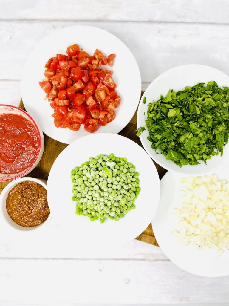 ingredients for turkey keema curry on a wooden board - tinned tomatoes, chopped tomatoes, chopped spinach, frozen peas, chopped onion and curry paste