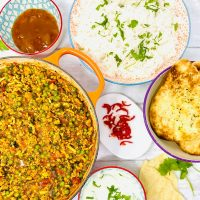 turkey mince curry - turkey keema made with spinach and peas served alongside fluffy boiled rice, naan breads, Indian mint sauce and mango chutney