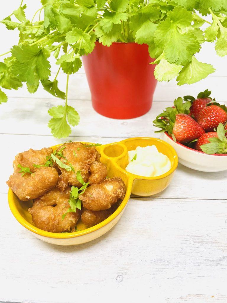 crispy prawns in beer batter with garlic mayonnaise dip, bowl of strawberries