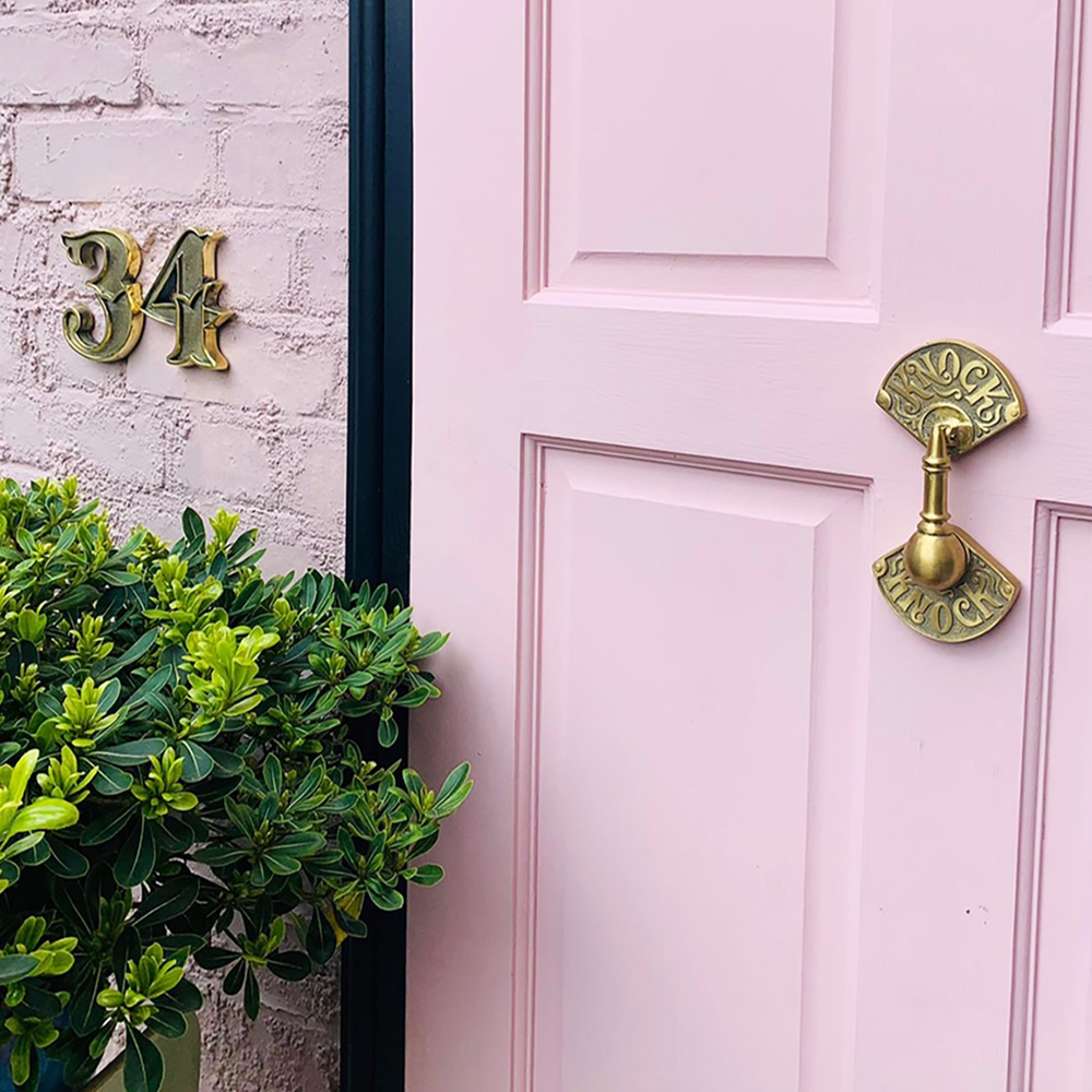curb appeal ideas - pastel pink bricks and pastel pink front door with a Knock Knock Door Knocker And Apex House Numbers - Unlacquered Brass, £39, www.gipsyhillhardware.com