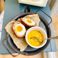gluten free scotch egg cut into half served on a metal tray with bowl of piccalilli