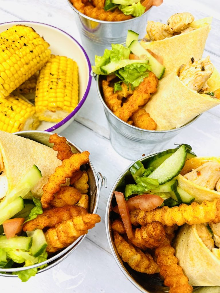 peri peri chicken wraps served with McCain chipotle chips and salad in a silver bucket. Bowl of corn cobs alongside