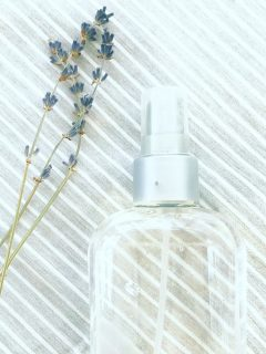 homemade peppermint pillow spray lay on bed nest to lavender blooms.