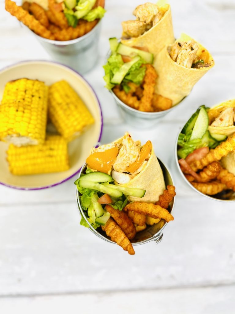 silver buckets holding peri peri chicken wraps, chipotle chips and side salad. Bowl of corn cobs served alongside.