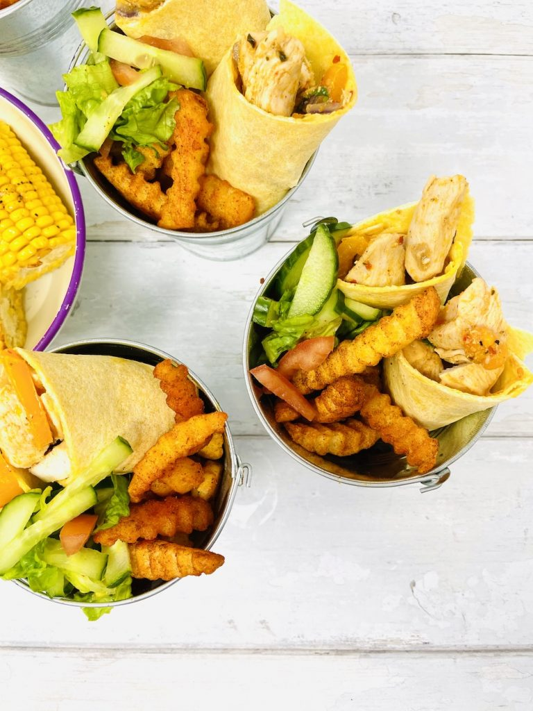 peri peri chicken wraps served with McCain chipotle chips and salad in a silver bucket