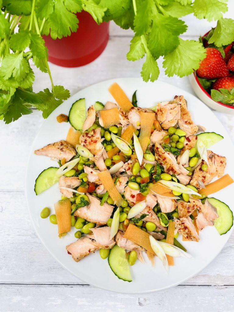 sweet chilli salmon salad with edamame beans, carrots and spring onions with a aromatic dressing. Bowl of strawberries alongside two forks next to the plate.