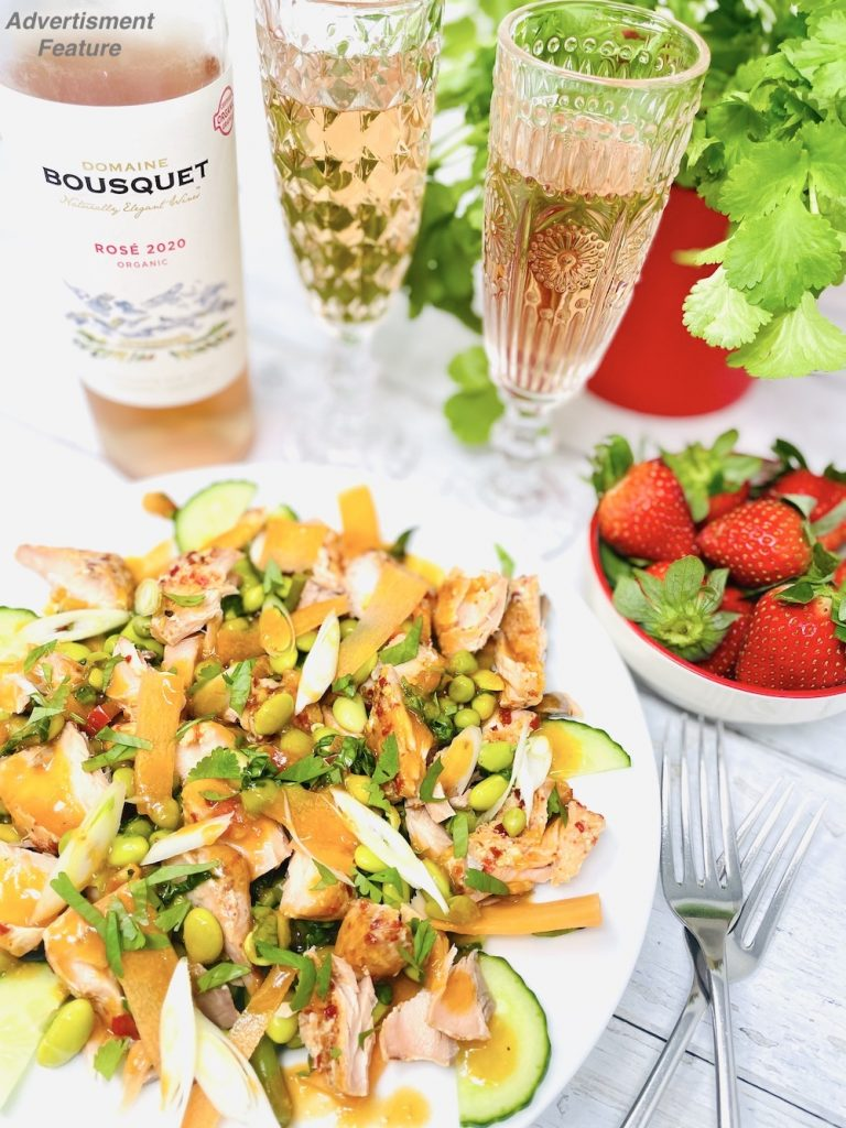 Domaine Bousquet Rosé wine poured into glasses and served alongside a sweet chilli salmon salad and bowl of strawberries - wines for summer 2021