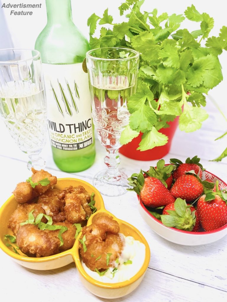 Wild Thing Sauvignon Blanc summer wine 2021 poured into two glasses and served alongside crispy beer battered prawns with a garlic mayonnaise dip