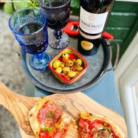 summer wines 2021 - Orlandi Contucci Ponno, La Regia Specula 2017   Montepulciano d'Abruzzo DOCG poured into blue glasses and served alongside salami pizza and bowl of marinated olives