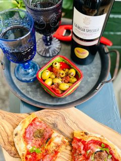 summer wines 2021 - Orlandi Contucci Ponno, La Regia Specula 2017 | Montepulciano d'Abruzzo DOCG poured into blue glasses and served alongside salami pizza and bowl of marinated olives