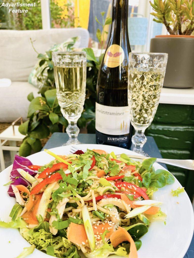 Kurtatsch Gewürztraminer wine poured into glasses and served alongside a spicy Szechuan chicken noodle salad