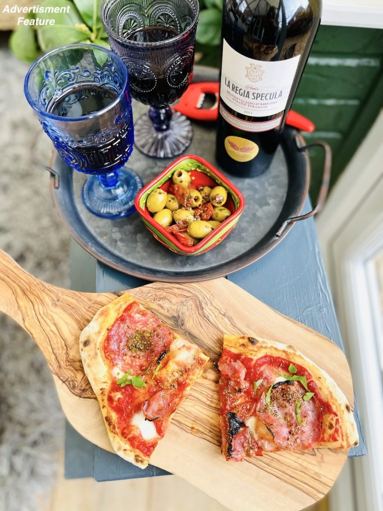 wines for summer 2021 - Orlandi Contucci Ponno, La Regia Specula 2017 | Montepulciano d'Abruzzo DOCG poured into blue glasses and served alongside salami pizza and bowl of marinated olives