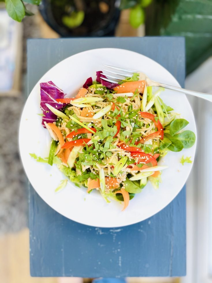 Szechuan chicken noodle salad with aromatic salad dressing served on a white plate, stood on a small grey side table.