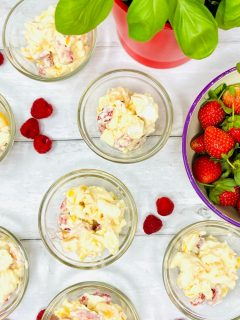 Eton mess with strawberries and mango served in small glass bowls