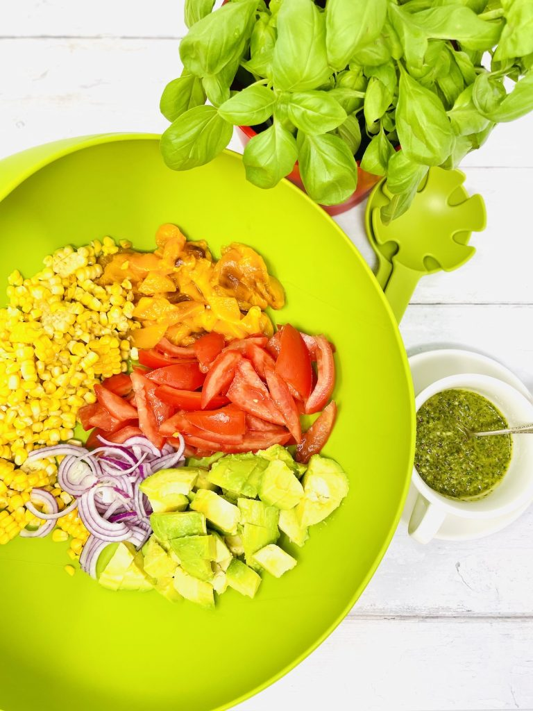 corn and avocado salad ingredients in a green Joseph Joseph salad bowl - chopped avocado, red onion, charred peppers, charred corn and vine tomatoes small pot of Chimichurri dressing to the side with a silver spoon in it