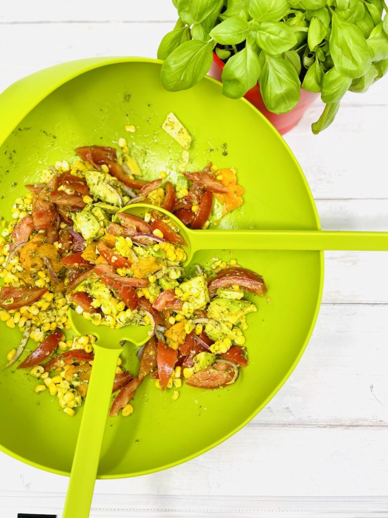 corn and avocado salad being tossed with salad servers in a bright green Joesph Joseph salad bowl