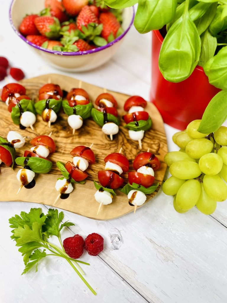 caprese skewers on a wooden graze board surrounded by bowl of strawberries, raspberries, potted basil plant and grapes.